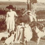 image of Woman, Children, and Dogs with Cart in Greenman Front Yard